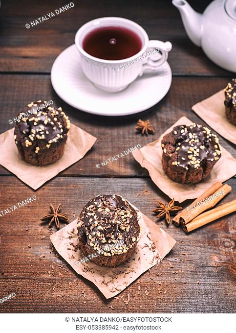 three chocolate muffins with nuts on a brown wooden background and a cup of tea