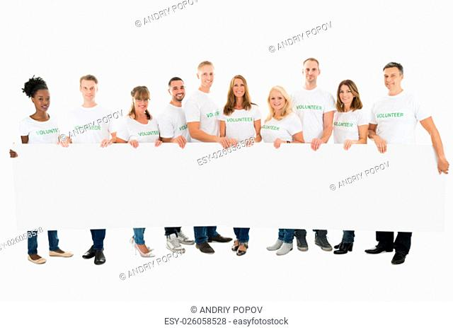 Full length portrait of confident volunteers holding blank billboard against white background