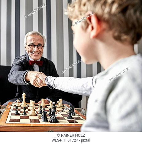 Grandfather and grandson shaking hands over chessboard