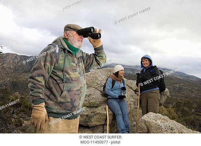 Senior man using binoculars in mountains