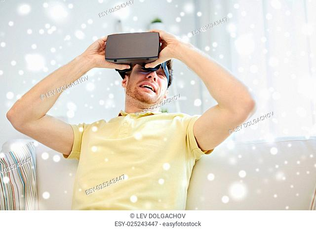 technology, augmented reality, gaming, entertainment and people concept - scared young man taking off virtual headset or 3d glasses while playing game over snow
