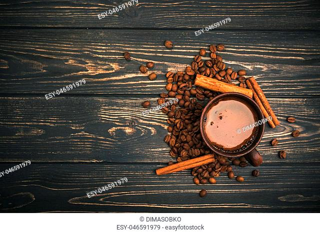 Cup of coffee with roasted beans and cinnamon on a wooden table. top view