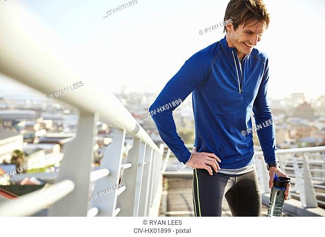 Smiling male runner resting drinking water on sunny urban footbridge