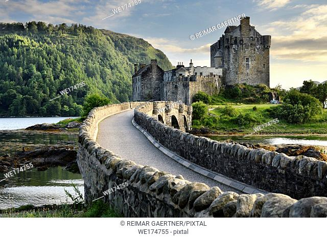 Evening light on restored Eilean Donan Castle on Island at three lochs with added stone arch footbridge Scottish Highlands Scotland UK