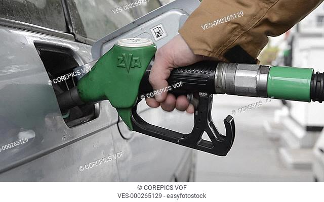 Man, ring a fuel nozzle from the gas tank of his car, and putting the lid back on