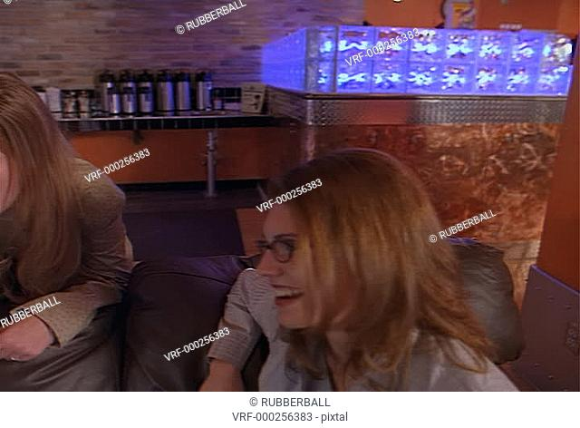 two caucasian women sit on black leather couch in cafe while another caucasian woman holding drink leans over couch and talks with them
