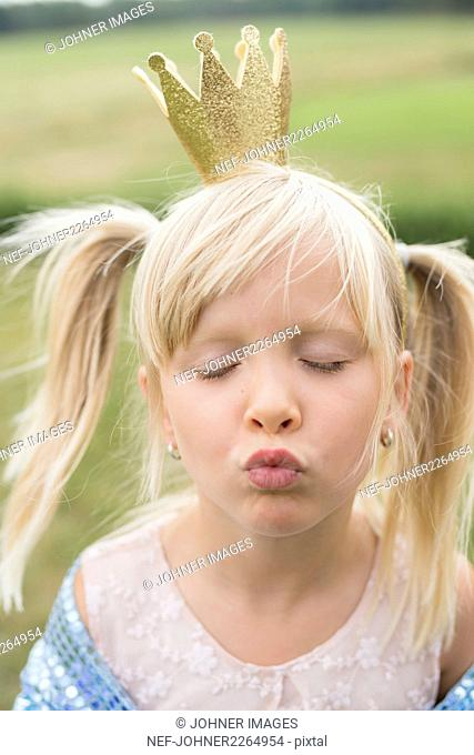 Girl dressed as princess blowing kiss