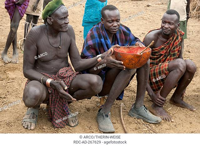 Nyangatom men sharing calabash of cow blood, Omo river valley, Ethiopia / Bume, Buma, Bumi