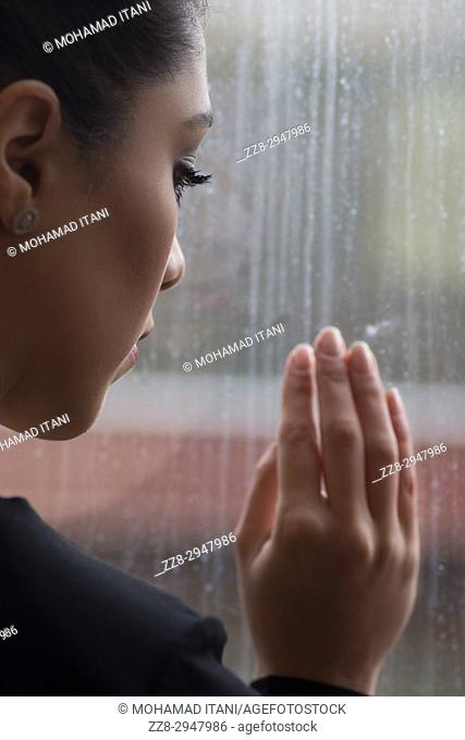 Rear view of a young Asian woman looking out of the window hand touching glass