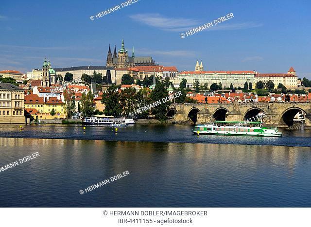 Prague Castle with St. Vitus Cathedral on Castle Hill Hradcny, Castle District, Vltava River, tourist boats, Prague, Czech Republic
