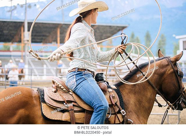 Caucasian cowgirl twirling lasso in rodeo