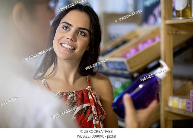 Woman looking at man holding soap dispenser in shop