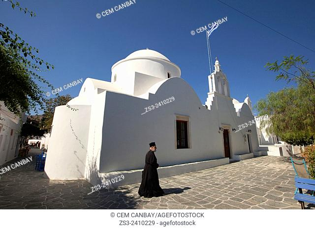 Priest walking in the streets of town center Hora with a white church at the background, Folegandros, Cyclades Islands, Greek Islands, Greece, Europe