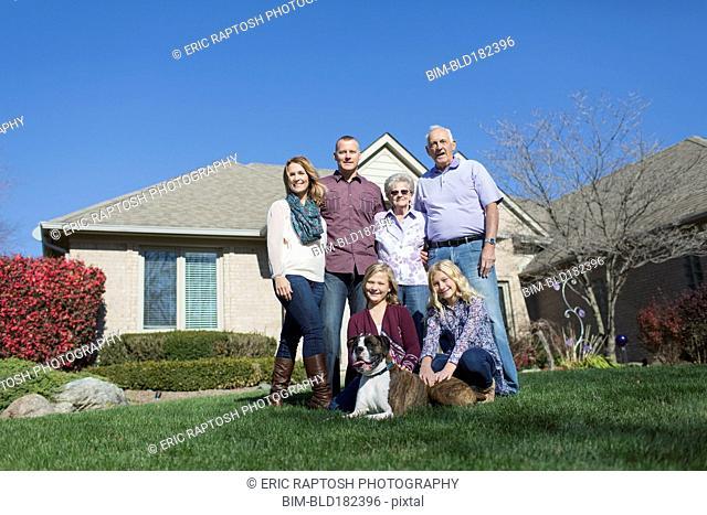 Caucasian multi-generation family smiling in yard