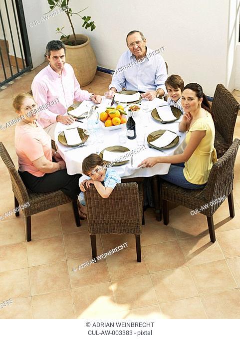 Multi-generational family having lunch on terrace, smiling, portrait