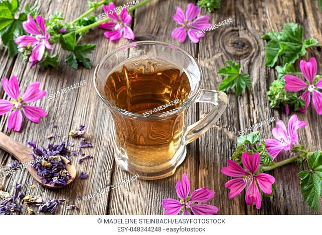 A cup of mallow tea with fresh malva sylvestris flowers on a table
