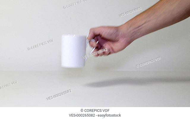 Man's arm ,placing a mug on a table, filling it with coffee, adding sugar, and stirring, before lifting the mug from the table. Loopable footage