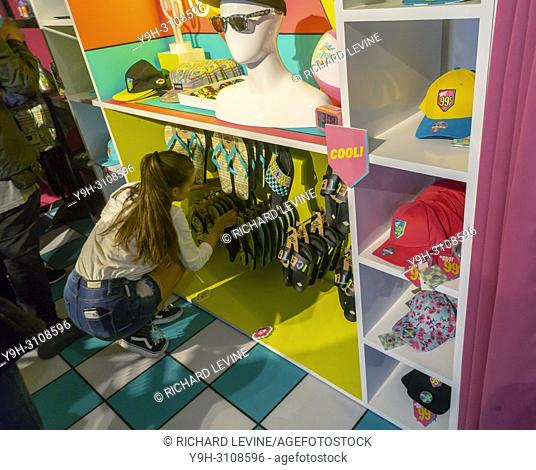 """A worker re-stocks merchandise in the AriZona Beverages """"""""Great Buy 99¢"""""""" pop-up store in Soho in New York on opening day, Wednesday, May 16, 2018"""