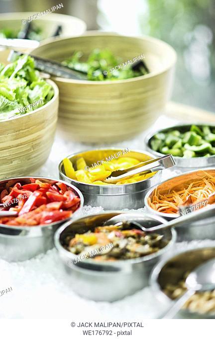 bowls of mixed fresh organic vegetables in modern salad bar display