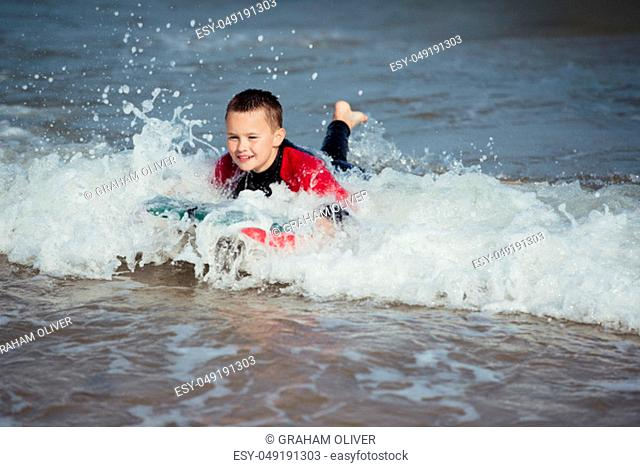 Little boy playing in the surf with a bodyboard