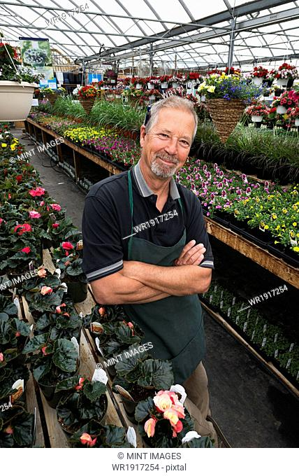 A man standing in a greenhouse with shelves of plants
