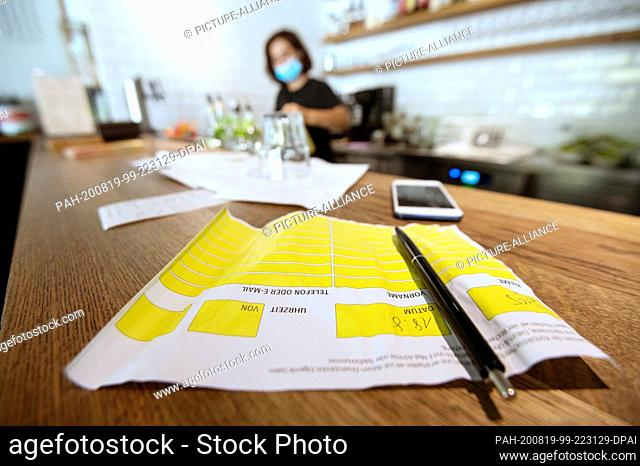 18 August 2020, Baden-Wuerttemberg, Stuttgart: An employee in a pizzeria wears a mouthguard, while on the counter there is a slip of paper for visitor...