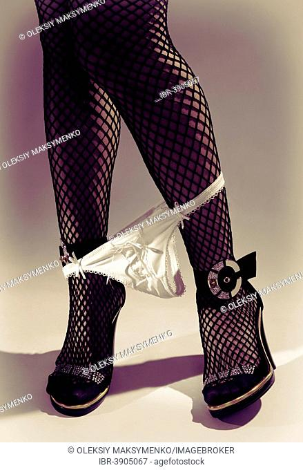 Woman's legs wearing fishnet stockings with her panties on her ankles