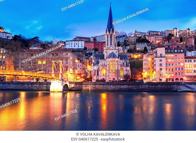 Panoramic view of Saint Georges church and footbridge across Saone river in the Old town during evening blue hour, Lyon, France