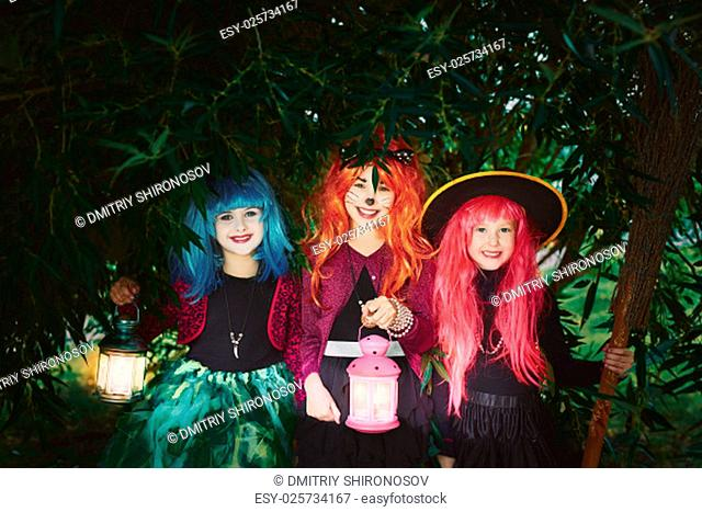 Little girls with lanterns and broom looking at camera outdoors