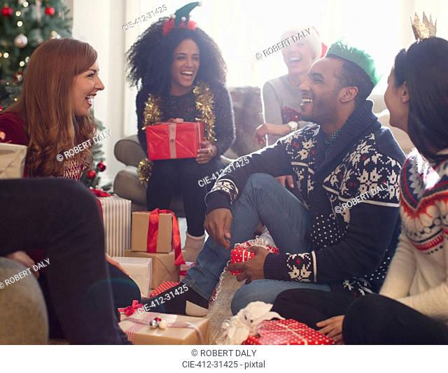 Laughing friends opening Christmas gifts in living room