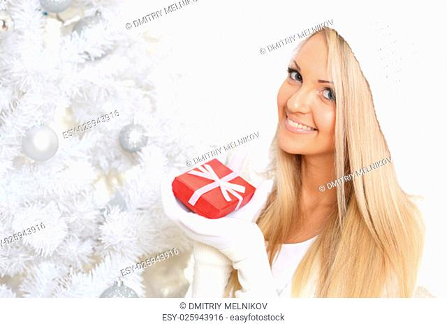 Young happy beautiful woman in winter clothes with gift box stands near Christmas tree on a white background