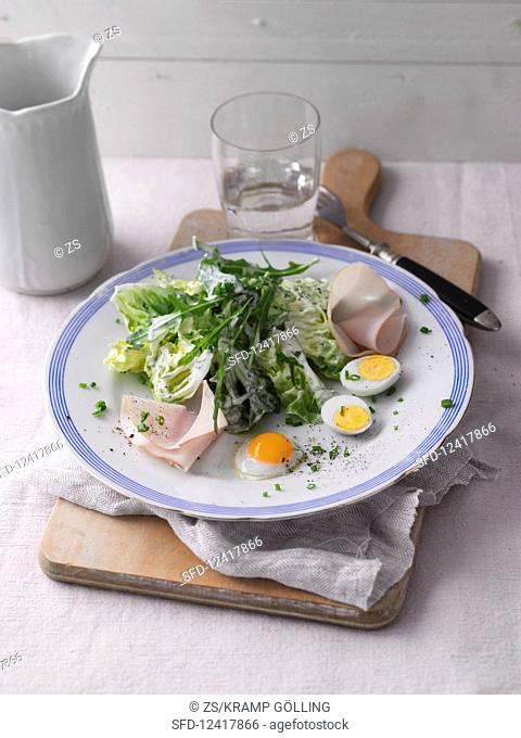 A mixed leaf salad with turkey breast and quail's eggs