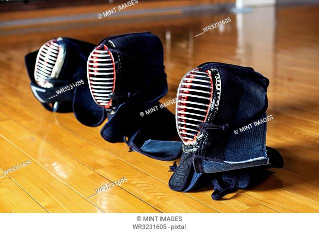 High angle close up of row of three Kendo masks on hardwood floor