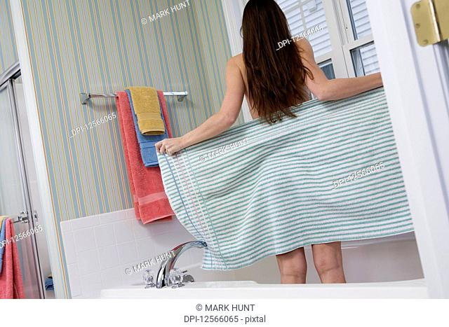 A young woman drying off with a towel in a bathtub