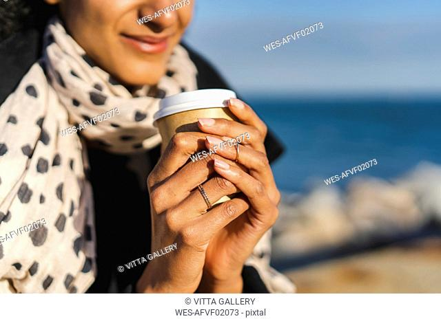 Woman's hands holding coffee to go, close-up