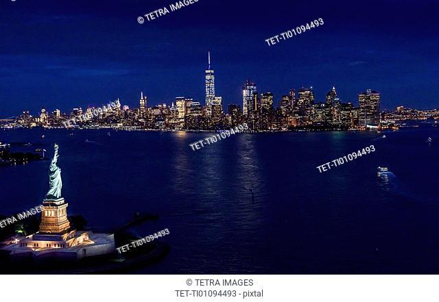 USA, New York, New York City, Manhattan, Aerial view of illuminated skyline with Statue of Liberty at night