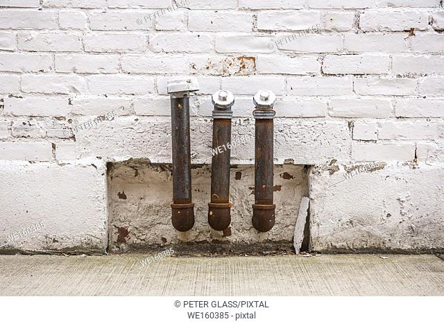 Three metal pipes attached to the side of a brick building
