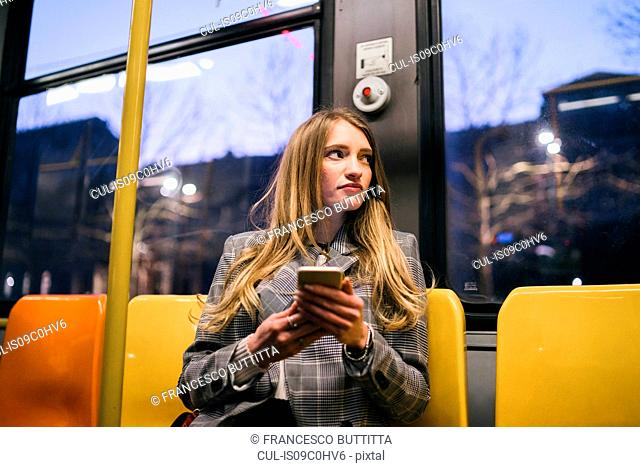 Young woman with long blond hair sitting in train carriage with smartphone at dusk