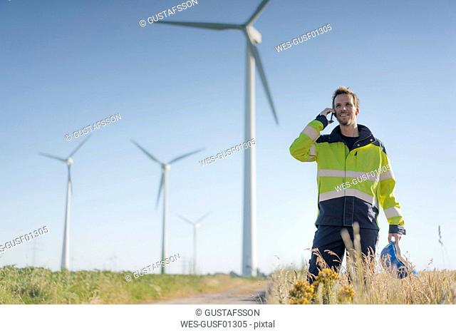 Smiling engineer standing in a field at a wind farm talking on cell phone