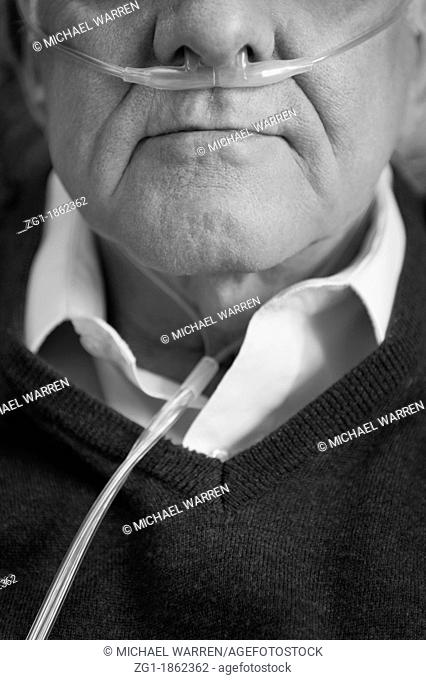 Closeup black and white portrait of an elderly man wearing oxygen nasal tube, black and white