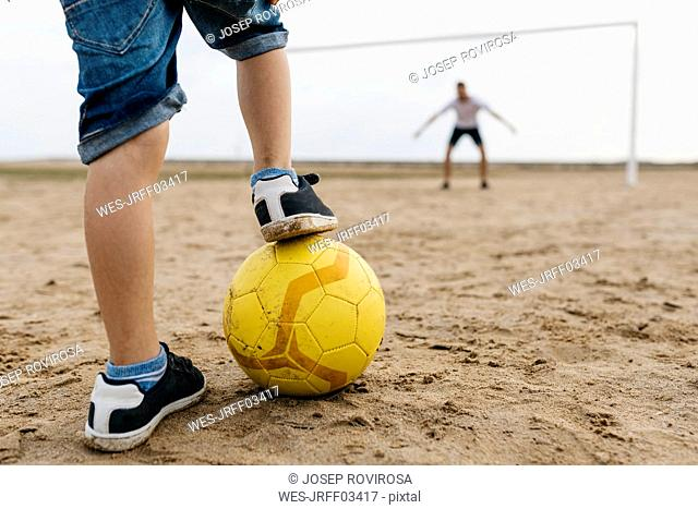Close-up of man and boy playing soccer on the beach