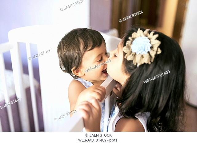 Sister kissing her little brother in bedroom