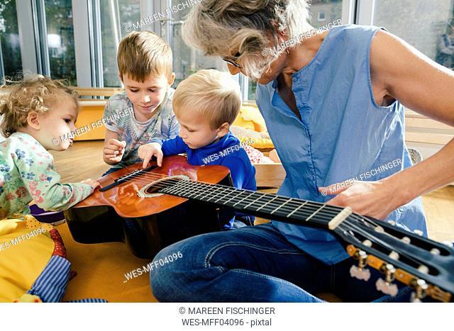 Pre-school teacher showing a guitar to children in kindergarten