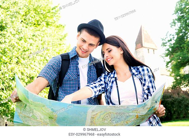 Traveling couple searching for their next destination with a map