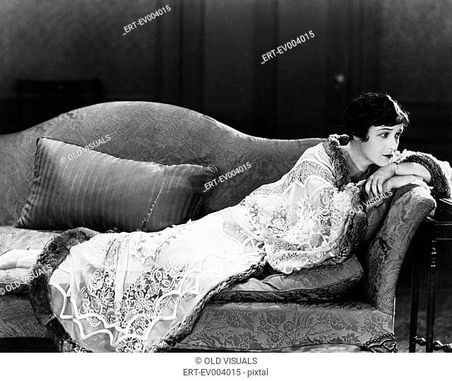 Woman lying on couch All persons depicted are not longer living and no estate exists Supplier warranties that there will be no model release issues