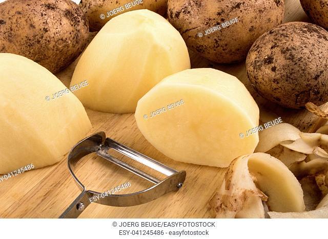 raw peeled organic potatoes on a wooden board