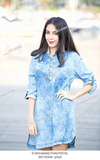 Beautiful young Lebanese woman standing outdoors hand on hip smiling