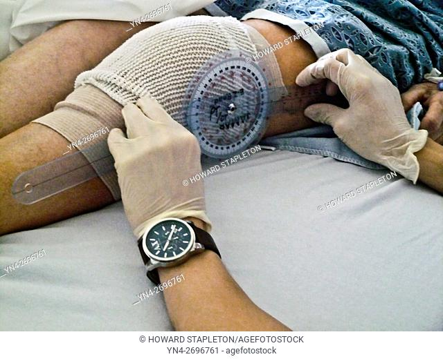 A physical therapist reads a goniometer (Medical protractor) to measure the range of motion on a patient following knee replacement surgery