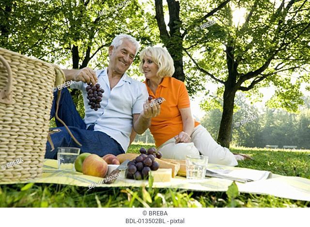mature couple sharing grapes at picnic