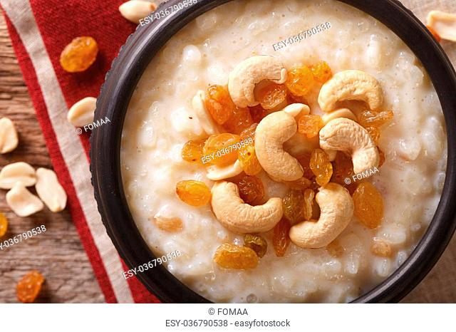 sweet rice pudding with nuts and raisins in a bowl close-up on the table. Horizontal view from above